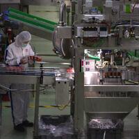 Sur cette photo du 27 février 2020, un employé contrôle les yaourts qui sortent de la chaîne de production de l'usine de produits laitiers à Pékin. Des journalistes ont été invités dans usine Mengniu Dairy Co. Ltd. cette semaine pour observer la relance des entreprises après les mesures d'arrêt de presque l'intégralité de la deuxième plus grande économie au monde. (AP Photo/Ng Han Guan)