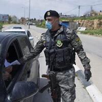 Un agent des forces de sécurité de l'Autorité palestinienne contrôle l'application des règles contre le COVID-19 dans la ville de Ramallah en Cisjordanie, le 23 mars 2020. (AP Photo/ Nasser Nasser)