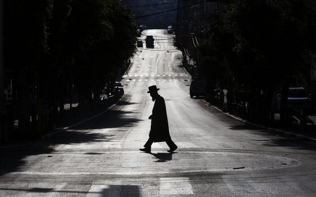 Un Juif ultra-orthodoxe traverse une rue déserte après les mesures prises par le gouvernement pour limiter  la propagation du coronavirus à Bnei Brak, le mercredi 8 avril 2020. (AP Photo/Oded Balilty)