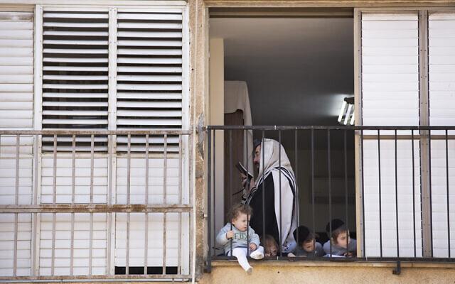 Un homme ultra-orthodoxe récite sa prière du matin dans son appartement alors que ses enfants regardent par la fenêtre lors d'un confinement imposé pour ralentir la propagation du coronavirus à Bnei Brak, le 8 avril 2020.  (AP Photo/Oded Balilty)