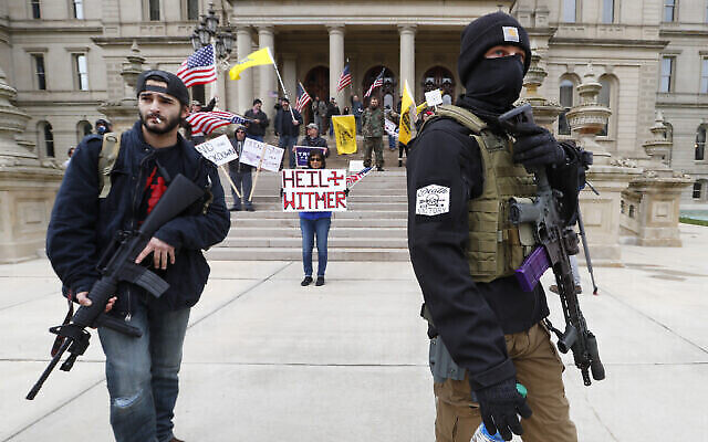 Des manifestants portent des armes devant les marches de bâtiment du Capitol de l'Etat du Michigan à Lansing, aux États-Unis, le 15 avril 2020. (Crédit : AP/Paul Sancya)