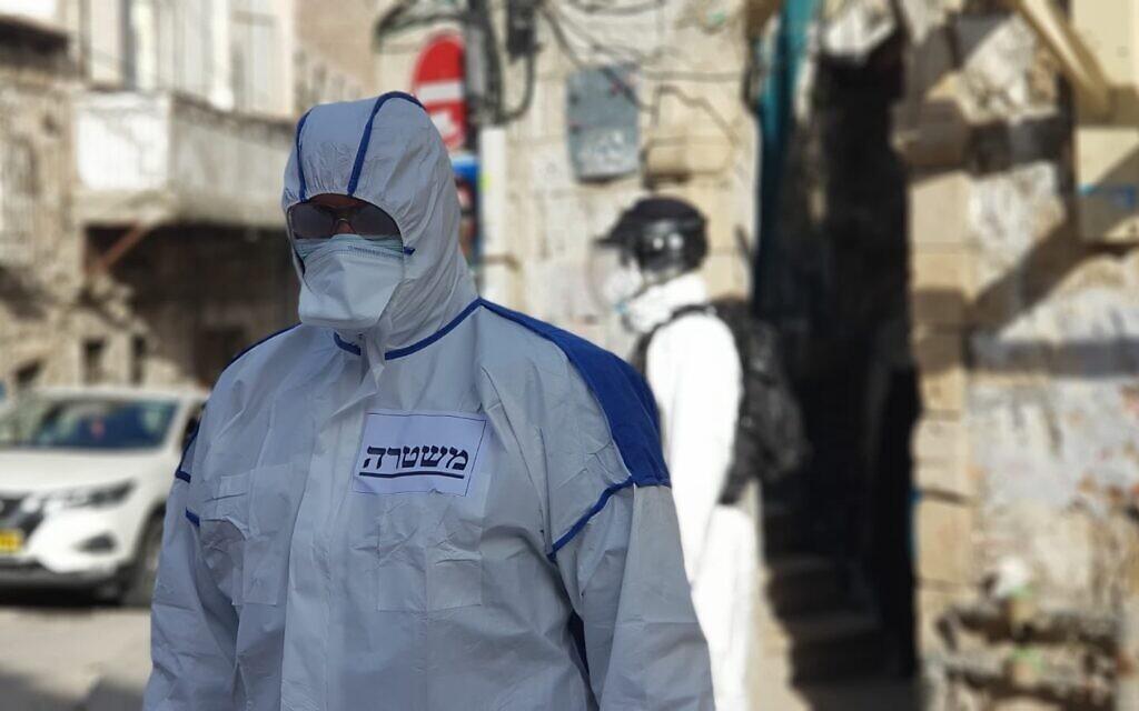 La police israélienne, portant des vêtements de protection, est dans le quartier de Mea Sherim de Jérusalem pour arrêter un homme contaminé au COVID-19 qui a enfreint les règles de quarantaine, le 6 avril 2020. (Crédit : police israélienne)