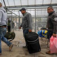 Des ouvriers palestiniens de la ville cisjordanienne d'Hébron portent leurs affaires personnelles en arrivant au point de passage de Tarqumiya pour entrer en Israël le 18 mars mars 2020. (Wisam Hashlamoun/Flash90)