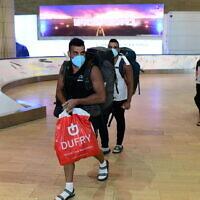 Des voyageurs israéliens, qui avaient été bloqués en Amérique du sud, arrivent à l'aéroport Ben Gurion, le 23 mars 2020, depuis Sao Paolo via New York. (Tomer Neuberg/Flash90)