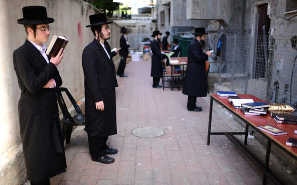 Des hommes juifs ultra-orthodoxes prient devant une yeshiva fermée dans la ville de Bnei Brak, le 26 mars 2020.  (Tomer Neuberg/Flash90)