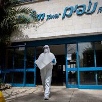 Un personnel de Magen David Adom portant un vêtement de protection teste au COVID-19 des habitants de la Tour Nofim, une résidence assistée, à Jérusalem le 27 mars 2020. (Yonatan Sindel/Flash90)