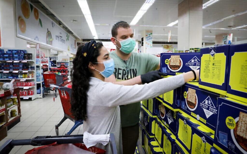Des gens portent des masques pour se protéger du coronavirus alors qu'ils achètent du matzah, un pain non levé traditionnellement consommé pour Pessah, dans un supermarché de Jérusalem, le 31 mars 2020. (Yossi Zamir/Flash90)
