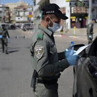 Un agent israélien de la Police des Frontières contrôle les documents d'un automobiliste à un barrage situé à la sortie de la ville ultra-orthodoxe de Bnei Brak, le 3 avril 2020. (Gili Yaari /Flash90)