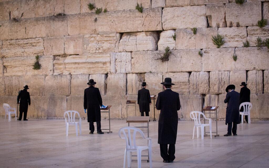 Des hommes juifs prient au mur Occidental presque désert dans la Vieille Ville de Jérusalem, le 7 avril 2020. (Nati Shohat/Flash90)