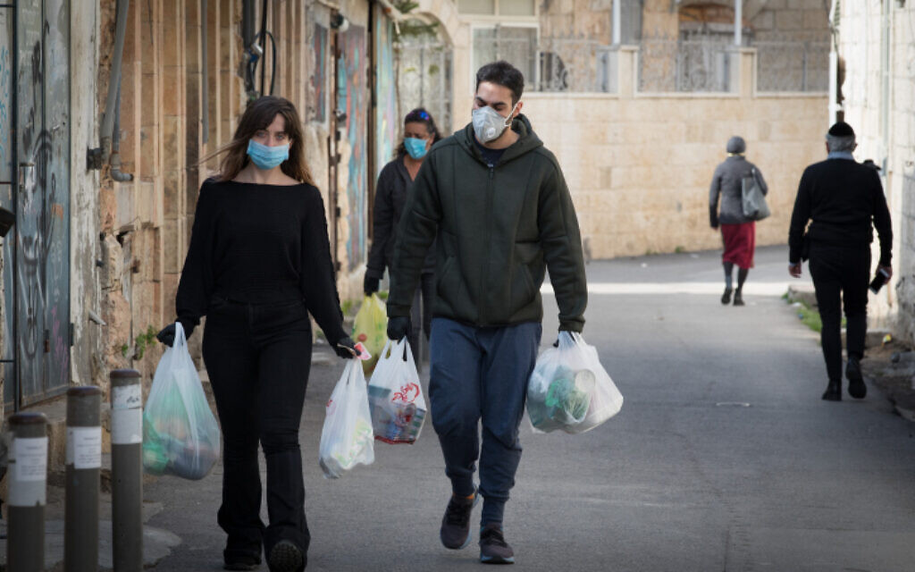 Des personnes avec des sacs de courses à Jérusalem, le 12 avril 2020.  (Nati Shohat/Flash90)