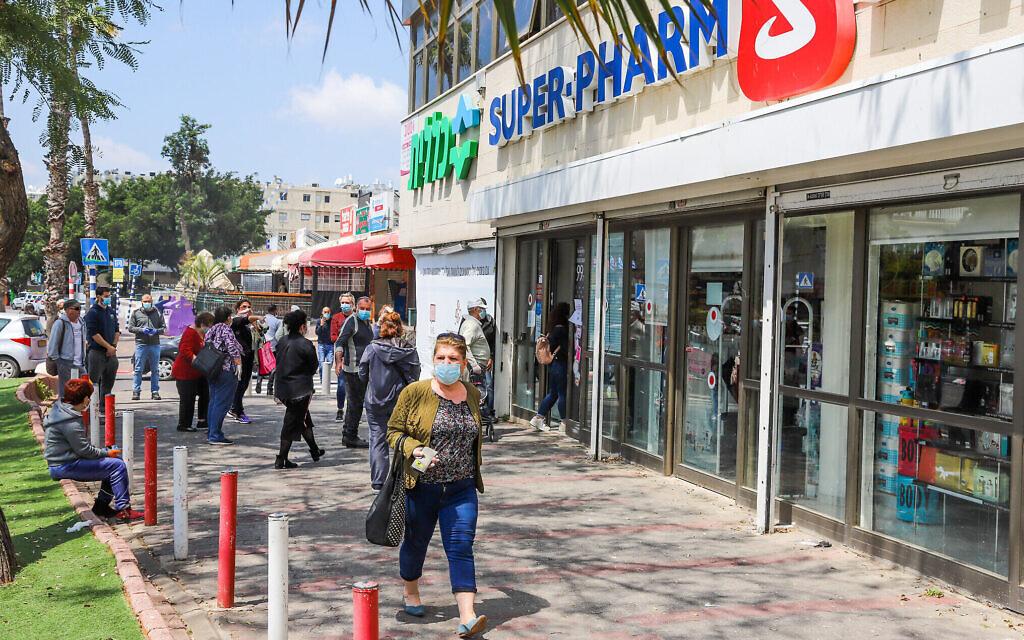 Des Israéliens devant une pharmacie dans la ville du centre du pays de Lod, le  12 avril 2020. ( Yossi Aloni/Flash90)