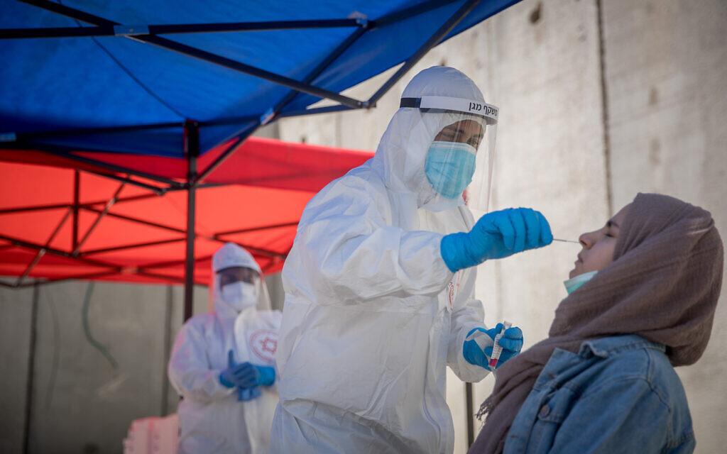 Des soignants du Magen David Adom  collectent des tests du coronavirus sur un site mobile le long de la barrière de sécurité autour du camp de réfugiés de Shuafat, à Jérusalem, le 16 avril 2020.  (Yonatan Sindel/Flash90)