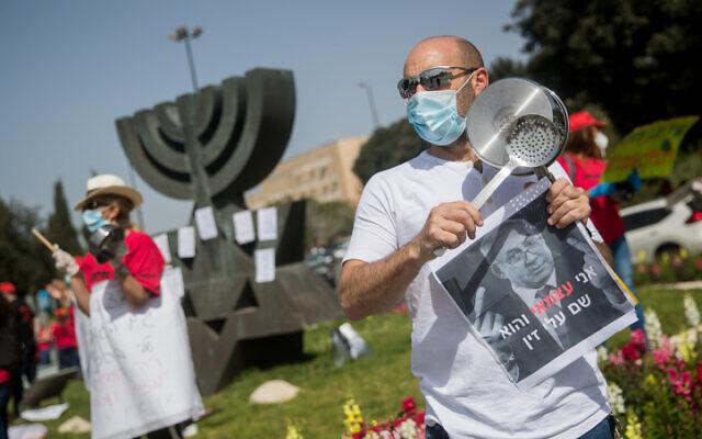 Des auto-entrepreneurs israéliens propriétaires de petites entreprises participent à une manifestation afin de demander une aide financière au gouvernement israélien devant le parlement israélien à Jérusalem, le 19 avril 2020. (Yonatan Sindel/Flash90)