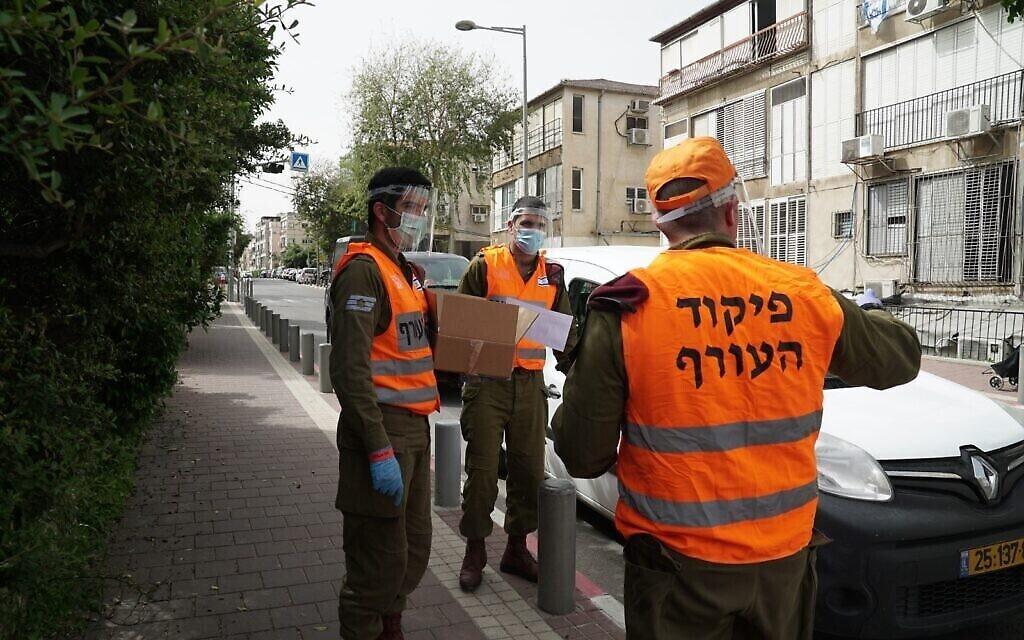 Des soldats israéliens donnent de la nourriture aux habitants de la ville de Bnei Brak dans le centre d'Israël. La ville a été largement coupée du reste du pays à cause de l'épidémie de coronavirus, le 5 avril 2020. (Crédit : Armée israélienne)
