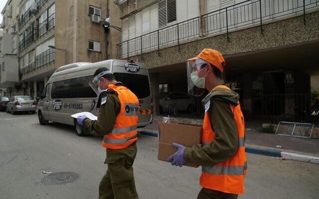 Des soldats israéliens donnent de la nourriture aux habitants de la ville de Bnei Brak dans le centre d'Israël. La ville a été largement coupée du reste du pays à cause de l'épidémie de coronavirus, le 5 avril 2020. (Crédit Armée israélienne)