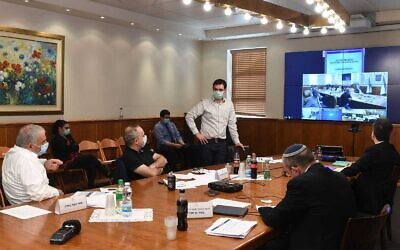 Le ministre de Finances Moshe Kahlon (gauche), le directeur adjoint du ministère de la Santé Moshe Bar Siman-Tov (debout) et d'autres officiels se rencontrent jeudi pour discuter de l'assouplissement des mesures de distanciation sociale mises en place pour lutter contre le coronavirus. (Bureau du Premier ministre)