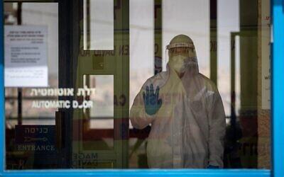 Un urgentiste du Magen David Adom, portant un équipement de protection, arrive pour tester au COVID-19 des résidents dans la maison de retraite Nofim le 27 mars 2020. (Yonatan Sindel / Flash90)