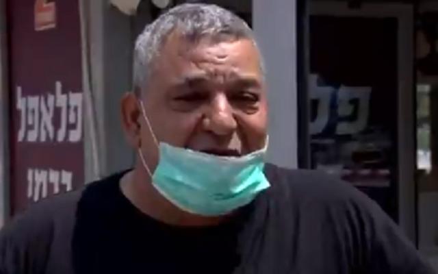 Yuval Carmi, propriétaire d'un magasin de falafel à Ashdod, montre son portefeuille vide, le 19 avril 2020 (Capture d'écran : Treizième chaîne)