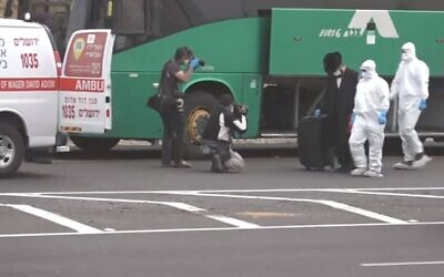 Un Israélien suspecté d'avoir sciemment pris un bus pour Jérusalem après avoir été testé positif au COVID-19 est accompagné par des urgentistes du  Magen David Adom du bus vers une ambulance le 5 avril 2020 (Capture d'écran : Douzième chaîne)