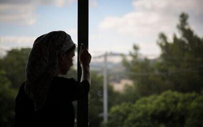 Une Juive orthodoxe regarde par la fenêtre d'un foyer pour femmes battues à Beit Shemesh, le 15 juillet 2014. (Crédit : Hadas Parush/Flash90)