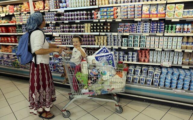 Une femme fait des courses avec son fils au supermarché Rami Levy dans le bloc d'implantations de Gush Etzion. (Nati Shohat/Flash90)