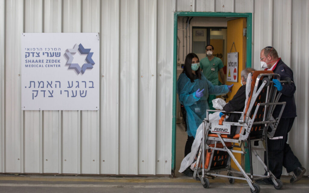 Des personnels du Magen David Adom et hospitaliers transportent un malade du coronavirus présumé à l'hôpital Shaare Zedek de Jérusalem, le 31 mars 2020 (Crédit : Nati Shohat /FLASH90)