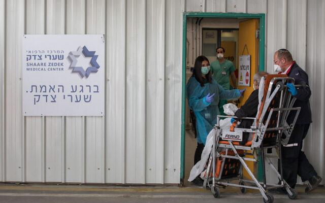 Des personnels du Magen David Adom et hospitaliers transportent un malade du coronavirus présumé à l'hôpital Shaare Zedek de Jérusalem, le 31 mars 2020 (Crédit : Nati Shohat/FLASH90)