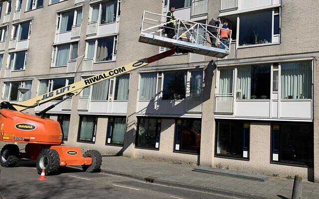 Les proches de Fiet Aussen s'apprêtent à la rencontrer depuis une grue installée à la fenêtre de sa maison de retraite juive à Amsterdam, le 15 avril 2020 (Autorisation : Riwal Holding Group via JTA)