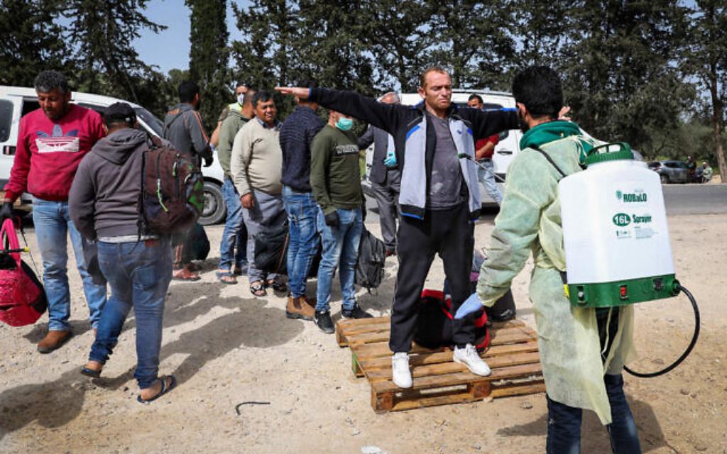 Des personnels palestiniens de la Santé désinfectent des ouvriers palestiniens de retour d'Israël à un barrage établi à Tarqumiya, le 27 mars 2020 (Crédit : Wisam Hashlamoun/Flash90)