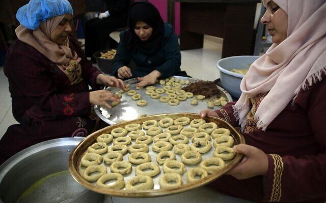 Des femmes palestiniennes préparent des gâteaux traditionnels avant les festivités de l'Aïd al-Fitr, célébrant la fin du mois sacré du ramadan, à Beit Lahia, dans le nord de la bande de Gaza, le 29 mai 2019 (Crédit :   MOHAMMED ABED / AFP)