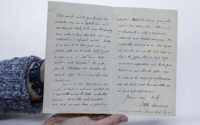 Un archiviste de la Bibliothèque nationale d'Israël présente une lettre datée de 1900 de James Murray, éditeur de l'Oxford English Dictionary, à la bibliothèque de Jérusalem, le 27 février 2020. (Menahem Kahana/AFP)