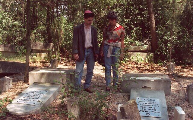 Un couple devant les tombes profanées de leurs proches, le 11 mai 1990, au cimetière juif de Carpentras, (Crédit : GABRIEL BOUYS / AFP)