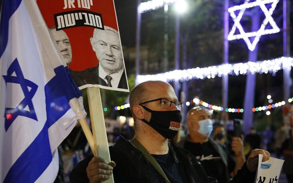 """Un manifestant israélien portant un masque de protection avec le slogan """"ministre du crime"""" en compagnie d'autres personnes respectant la distanciation de deux mètres imposée par le coronavirus brandit un panneau avec les visages du Premier ministre Benjamin Netanyahu et de Benny Gantz, ex-chef de Kakhol lavan, lors d'une manifestation sur la place Rabin de Tel Aviv, le 9 mai 2020 (Crédit : JACK GUEZ / AFP)"""