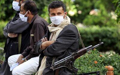 Un combattant appartenant aux rebelles houthis du Yémen porte un masque facial et des gants en latex et en lançant un fusil d'assaut à kalachnikov. Ces volontaires font partie d'une initiative communautaire visant à prévenir la propagation du COVID-19 qui se propage dans la capitale du Yémen, Sanaa, le 14 mai 2020. (Crédit :  MOHAMMED HUWAIS / AFP)