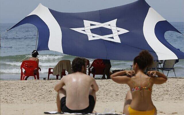 Les Israéliens profitent des plages dans un contexte de hausse des températures dans la ville côtière de Tel Aviv malgré les restrictions causées par le COVID-19, le 16 mai 2020 (Crédit :  JACK GUEZ / AFP)
