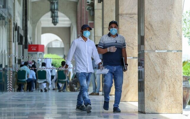 Des individus portent un masque de protection, dans les rues de Doha, au Qatar, le 17 mai 2020. (Crédit : KARIM JAAFAR / AFP)