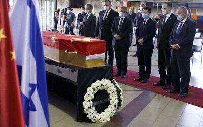 Des officiels chinois rendent hommage à la dépouille de l'ambassadeur chinois Du Wei dans un cercueil recouvert d'un drapeau, lors d'une cérémonie à l'aéroport international Ben Gurion à proximité de Tel Aviv, le 20 mai 2020. (Photo par JACK GUEZ / AFP)