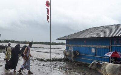 Des résidents passent à côté d'un drapeau signalant un grand danger avant l'arrivée prévue du cyclone Amphan, à Dacope dans la région de Khulna, le 20 mai 2020. (Photo par Munir uz Zaman / AFP)