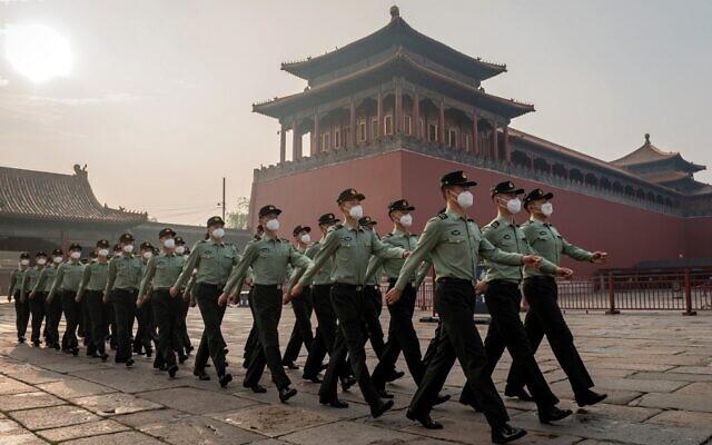 Des soldats de l'Armée populaire de libération défilent devant l'entrée de la Cité interdite lors de la cérémonie d'ouverture de la Conférence consultative politique du peuple chinois (CCPPC) à Pékin, le 21 mai 2020. (Crédit : NICOLAS ASFOURI / AFP)