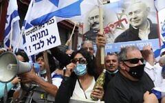 Des partisans de Netanyahu agitent des drapeaux et une affiche représentant le Premier ministre Benjamin Netanyahu et l'officier français Alfred Dreyfus, injustement condamné pour trahison en 1895, lors d'une manifestation devant le tribunal de Jérusalem  le 24 mai 2020.  (Photo par Menahem KAHANA / AFP)