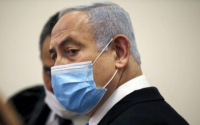 Le Premier ministre Benjamin Netanyahu, portant un masque de protection, dans la salle d'audience du tribunal de district de Jérusalem, le 24 mai 2020, au début de son procès pour corruption. (Ronen Zvulun / POOL / AFP)