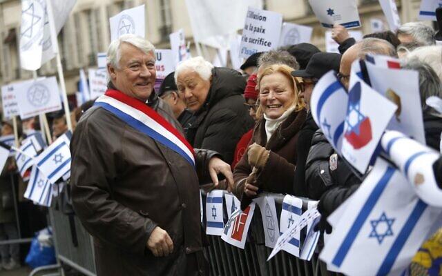 Le maire du 16e arrondissement Claude Goasguen salue la foule lors d'une manifestation à Paris contre la conférence de paix au Moyen-Orient qui se déroule dans la capitale française, le 15 janvier 2017. (Crédit : Pierre CONSTANT / AFP)