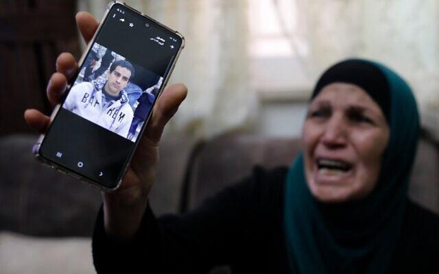 La mère d'un Palestinien atteint de troubles autistiques que la police aurait tué, croyant qu'il était armé, pleure en montrant la photo de son fils sur son téléphone au domicile familial de Jérusalem-Est, le 30 mai 2020 (Crédit : Ahmad GHARABLI / AFP)