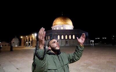 Un homme prie devant le Dôme du Rocher dans l'enceinte de la mosquée Al-Aqsa, troisième site le plus sacré de l'Islam, dans la Vieille Ville de Jérusalem, le 31 mai 2020, après sa fermeture pendant plus de deux mois en raison de la pandémie de coronavirus. (Crédit : Ahmad GHARABLI / AFP)