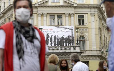 Des gens devant une bannière montrant des victimes exécutées par pendaison en 1945 par le régime croate pro-nazi oustachi pendant la Seconde Guerre mondiale, à Sarajevo, en Bosnie, le 16 mai 2020. (Crédit : AP / Kemal Softic)
