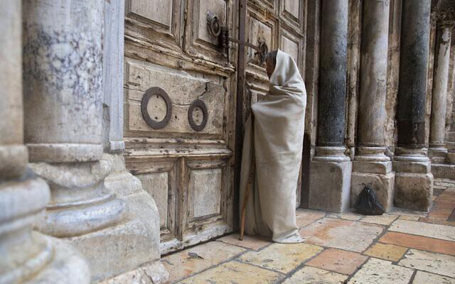 Un fidèle chrétien devant la porte fermée de l'église du Saint-Sépulcre, considérée par de nombreux chrétiens comme le site de la crucifixion et de l'enterrement de Jésus-Christ, à Jérusalem, le 10 avril 2020. (Crédit : AP Photo / Sebastian Scheiner)