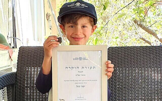 Imri Elya, 6 ans, originaire du kiccoutz Nirim, a découvert la pièce cananéenne au cours d'une randonnée avec ses parents au Tel Gama (ville cananéenne de Yarza) au mois de mars 2020 (Crédit : Autorité israélienne des antiquités)