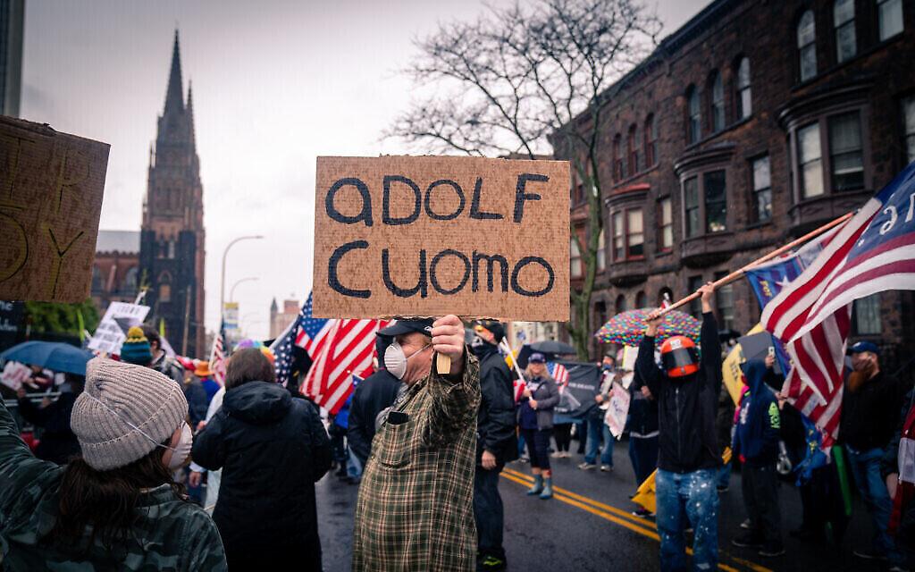 Un manifestant anti-confinement compare le gouverneur de New York Andrew Cuomo à Adolf Hitler lors d'une manifestation devant la résidence du gouverneur dans la capitale de l'État d'Albany, New York, le 1er mai 2020. (Crédit : Luke Tress/Times of Israël)