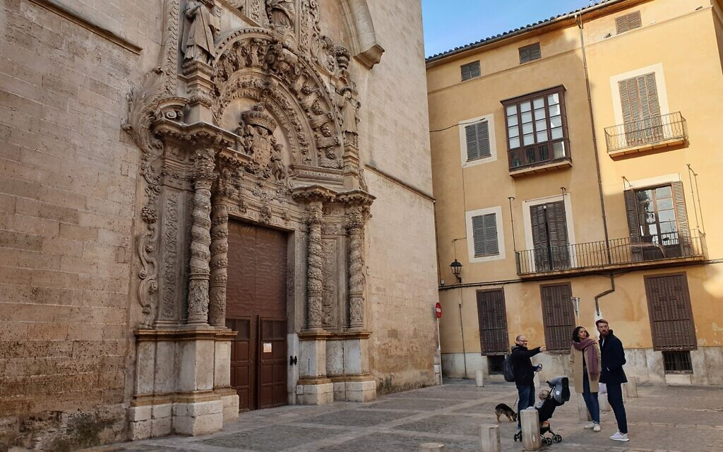 Dani Rotstein, le doigt en l'air, présente à des touristes allemands une église qui était une synagogue dans le passé à Palma de Majorque, le 11 février 2019 (Crédit : Cnaan Liphshiz/ JTA)