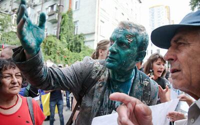 Le fondateur d' l'AntAC Vitaliy Shabunin aspergé d'un liquide antiseptique vert pendant une manifestation anti-corruption en Ukraine, le 17 juillet 2018 (Crédit :  Vyacheslav Ratynskyi / UNIAN)
